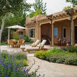 Foto di un patio o portico stile americano di medie dimensioni e dietro casa con pavimentazioni in pietra naturale e un tetto a sbalzo