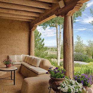 Immagine di un patio o portico stile americano di medie dimensioni e dietro casa con un focolare, pavimentazioni in pietra naturale e un tetto a sbalzo