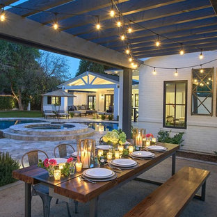 Inspiration for a large transitional backyard stone patio remodel in Phoenix with a pergola