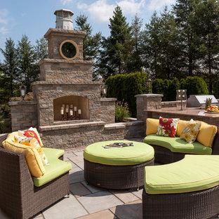 Idee per un patio o portico chic con un caminetto, pavimentazioni in cemento e nessuna copertura