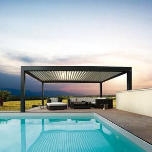 Immagine di un grande patio o portico design dietro casa con un tetto a sbalzo