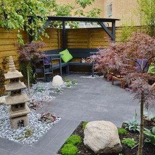 Immagine di un piccolo patio o portico etnico in cortile con pavimentazioni in pietra naturale
