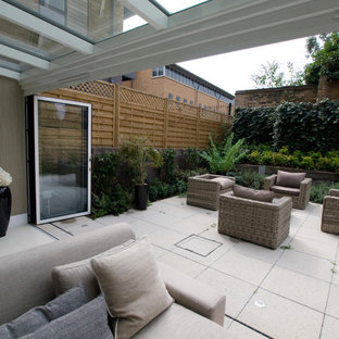 Photo of a small contemporary back patio in Cambridgeshire with a living wall, concrete paving and a roof extension.