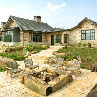 Ejemplo de patio rústico, sin cubierta, en patio trasero, con brasero y adoquines de piedra natural