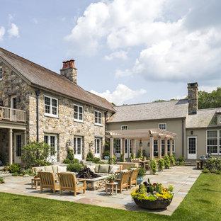 Foto di un ampio patio o portico tradizionale dietro casa con un focolare, pavimentazioni in pietra naturale e una pergola