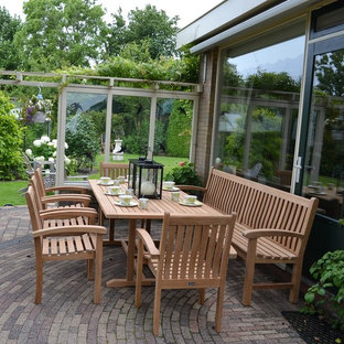 Inspiration for a large scandi back patio in Other with a potted garden, brick paving and an awning.