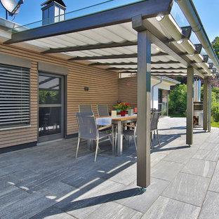 Idéer för att renovera en mellanstor funkis uteplats längs med huset, med granitkomposit och markiser