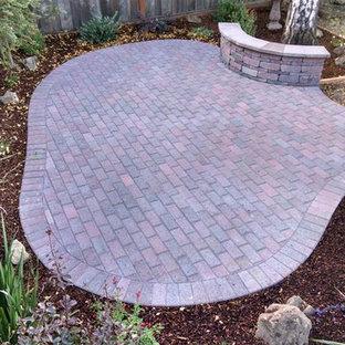 Ejemplo de patio tradicional, de tamaño medio, sin cubierta, en patio trasero, con jardín de macetas y adoquines de piedra natural