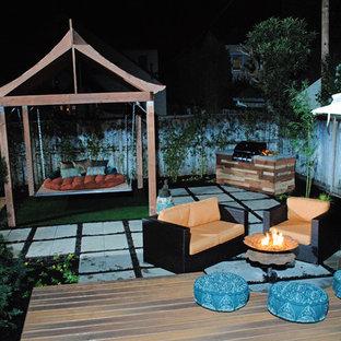 Esempio di un patio o portico etnico di medie dimensioni e dietro casa con un focolare, pavimentazioni in cemento e una pergola
