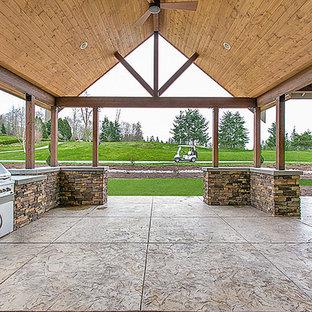 Immagine di un grande patio o portico american style dietro casa con cemento stampato e un tetto a sbalzo
