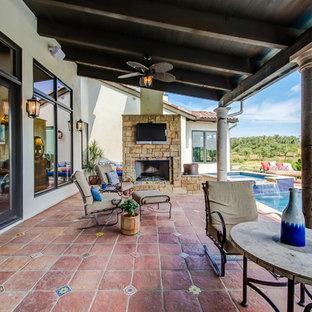 Ispirazione per un grande patio o portico american style dietro casa con piastrelle e un tetto a sbalzo