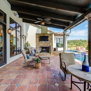 Patio kitchen - large southwestern backyard tile patio kitchen idea in Austin with a roof extension