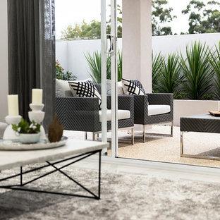 Ispirazione per un patio o portico design di medie dimensioni e dietro casa con graniglia di granito e un tetto a sbalzo