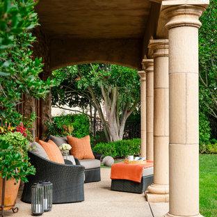 Ejemplo de patio de estilo americano, de tamaño medio, en patio trasero y anexo de casas, con suelo de hormigón estampado