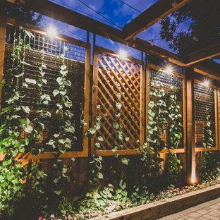 Ispirazione per un grande patio o portico chic dietro casa con pavimentazioni in cemento e una pergola