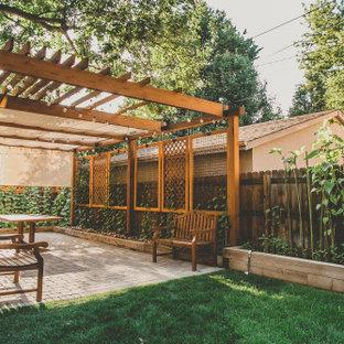 Immagine di un grande patio o portico classico dietro casa con pavimentazioni in cemento e una pergola
