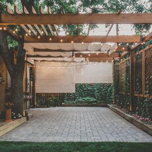 Ispirazione per un grande patio o portico tradizionale dietro casa con pavimentazioni in cemento e una pergola