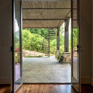 Ispirazione per un patio o portico stile americano dietro casa e di medie dimensioni con cemento stampato e un tetto a sbalzo