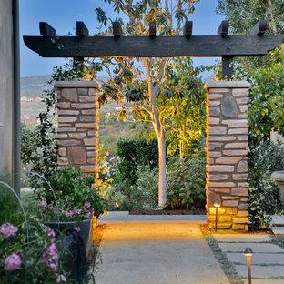 Modelo de patio mediterráneo, de tamaño medio, en patio lateral, con jardín de macetas, adoquines de hormigón y pérgola