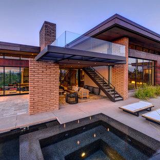 Exemple d'une grande terrasse arrière moderne avec un foyer extérieur, du carrelage et une extension de toiture.