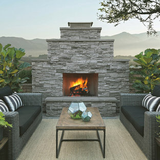 Example of a transitional concrete paver patio design in San Diego with a fire pit and no cover