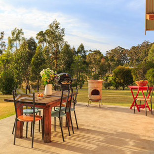 This is an example of a country backyard patio in Other with concrete slab and no cover.