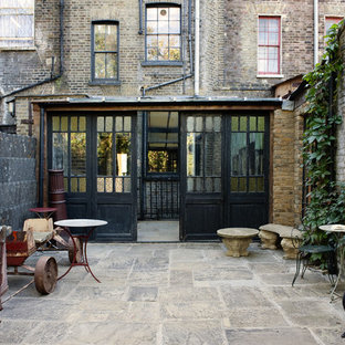Rustic courtyard patio in London with no cover.