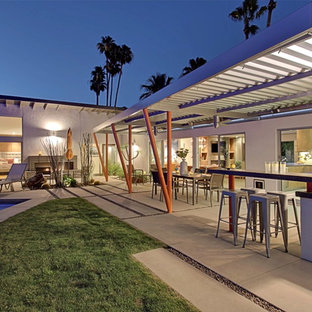 Large mid-century modern backyard concrete paver patio kitchen photo in Other with an awning