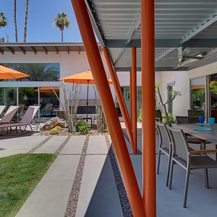 Inspiration for a large 1960s backyard concrete paver patio kitchen remodel in Los Angeles with a pergola