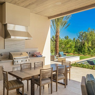 Inspiration for a contemporary backyard patio kitchen remodel in Orange County with a roof extension
