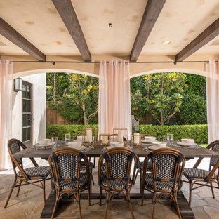 Tuscan stone patio photo in San Diego with a roof extension