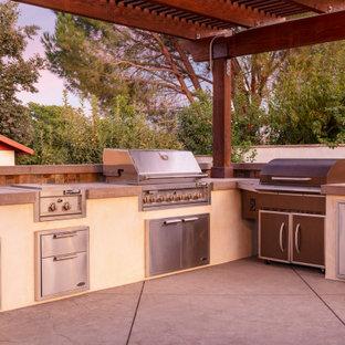 Idee per un grande patio o portico country dietro casa con pavimentazioni in cemento e una pergola