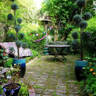 Ispirazione per un patio o portico eclettico dietro casa con pavimentazioni in pietra naturale e nessuna copertura