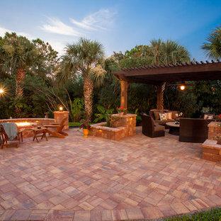 Esempio di un ampio patio o portico tradizionale dietro casa con un focolare, pavimentazioni in pietra naturale e una pergola