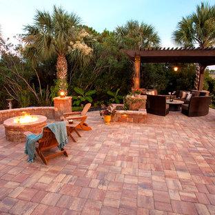 Foto di un ampio patio o portico chic dietro casa con un focolare, pavimentazioni in pietra naturale e una pergola