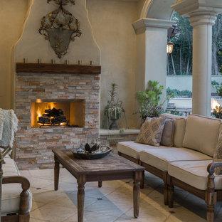 Idee per un patio o portico mediterraneo dietro casa con graniglia di granito e un parasole