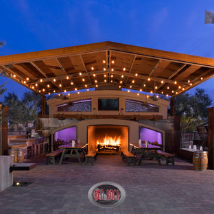 This is an example of an expansive country back patio in Phoenix with an outdoor kitchen, concrete paving and an awning.