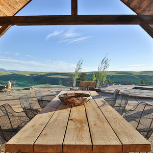 Example of a large mountain style backyard stone patio design in Other with a fire pit and a roof extension