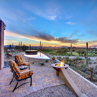 Inspiration for a southwestern backyard brick patio remodel in Phoenix with a fire pit and no cover