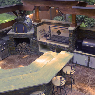 Inspiration for a mid-sized contemporary backyard stamped concrete patio kitchen remodel in Seattle with a roof extension