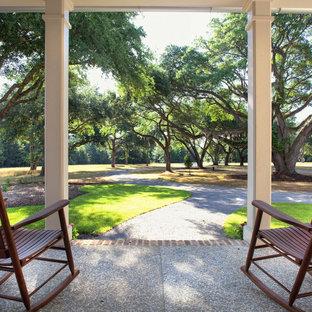 Esempio di un patio o portico chic di medie dimensioni e davanti casa con graniglia di granito e un tetto a sbalzo