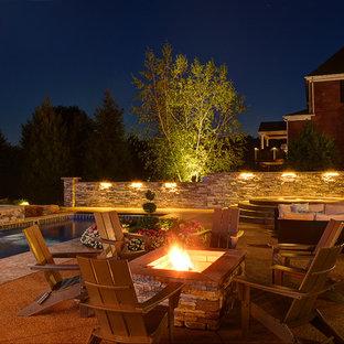 Esempio di un grande patio o portico american style dietro casa con un focolare