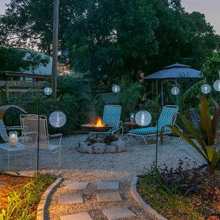 Aménagement d'une grande terrasse arrière romantique avec un foyer extérieur et du gravier.