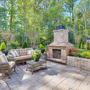 Inspiration pour une terrasse arrière style shabby chic de taille moyenne avec un foyer extérieur et des pavés en béton.