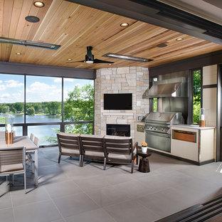 Immagine di un patio o portico design con piastrelle e un tetto a sbalzo