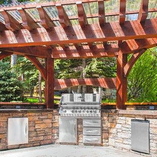 Foto di un patio o portico rustico di medie dimensioni e dietro casa con pavimentazioni in cemento e una pergola