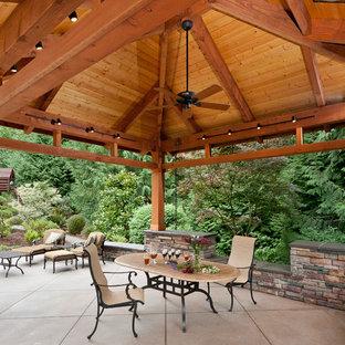 Ejemplo de patio tradicional, grande, en patio trasero, con cenador, cocina exterior y losas de hormigón