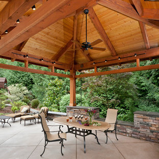 Example of a large classic backyard concrete patio kitchen design in Seattle with a gazebo