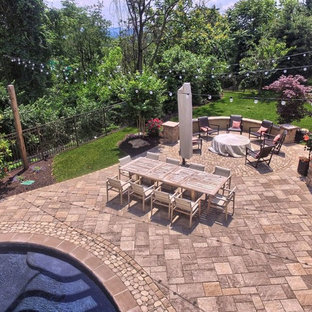 Photo of a large contemporary back patio in Philadelphia with an outdoor kitchen, concrete paving and a roof extension.