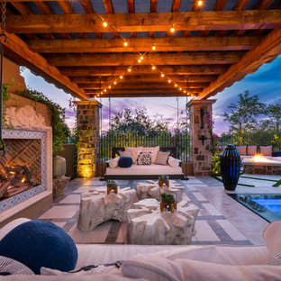 Idee per un ampio patio o portico shabby-chic style dietro casa con un focolare, pavimentazioni in pietra naturale e un gazebo o capanno